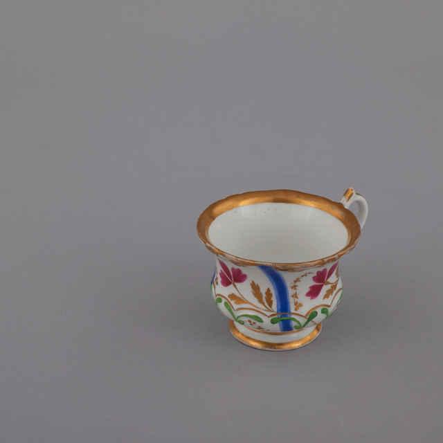 Šálka, porcelán, biela glazúra, maľovaný dekor, členenie modrými pásmi, purpurové trojlupeňové kvety, zlaté lístky, plastické listy, pozlátený okraj s okrídlenými hlavičkami, v. 6,4, horný priemer 8,8, šírka s uchom 11 cm