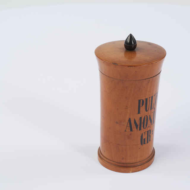 Stojatka drevo, sústruhovaná, lakovaná, bledohnedá, s pätkou a vrchnákom s čiernou úchytkou tvaru olivy, signatúra čierna PULV:AMONIAC:GR:. Kon.19.stor., v-145mm, p. 70mm