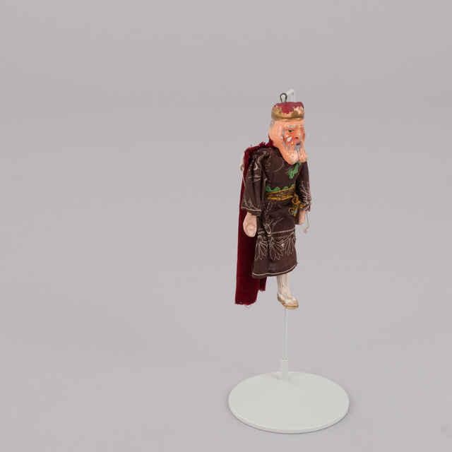 Bábka divadelná, sadra, kráľ, nemá pôvodné oblečenie, hnedé šaty, bordovo zlatá koruna, sivé fúzy a brada, chýba mu jedna noha, zlaté topánky, chýba vodiaci drôt a vahadlo, v. 17cm