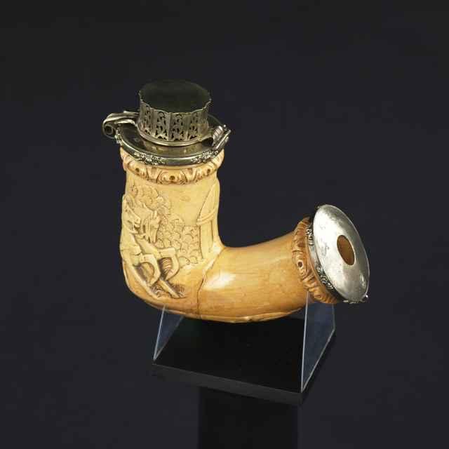 Fajka z bielej hliny, veľká, napustená do žlta, reliéf: trúbiaci jazdec na dvojkolesovom voze s koňmi, v spodnej časti štylizovaný ornament, po oboch stranách otvorov jemné strieborné kovanie, fajka v polovici zleptaná