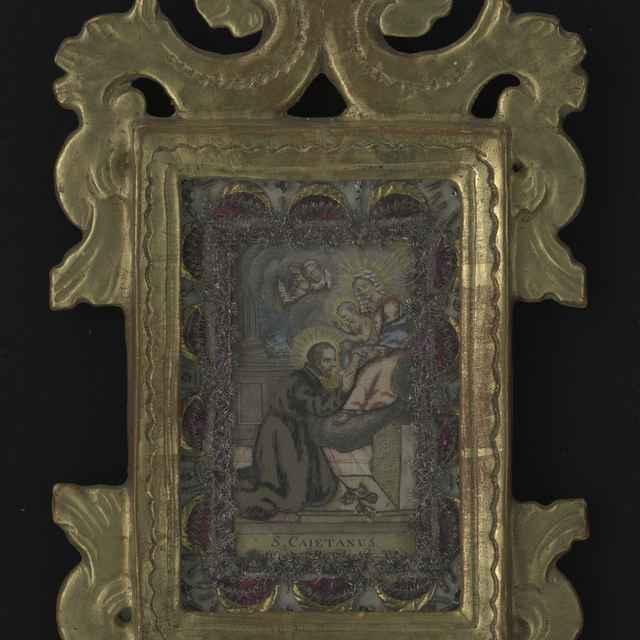 Obraz kláštorný v ráme - sv.Kajetán, kolorovaná tlač, dracúnová výzdoba, výzdoba z kovových nití a staniolu, ozdobný pozlátený rám, 18. stor., 30,5x17,5 cm