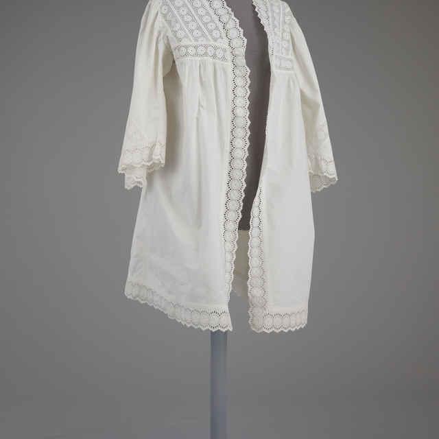 Kabátik česací, biele plátno, dĺ. 90cm, zošité pruhy čipky, bez zapínania
