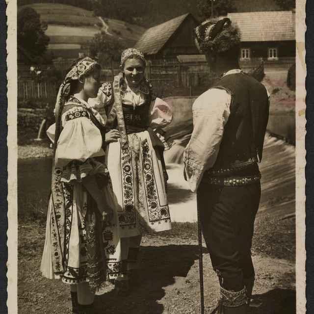 čiernobiela pohľadnica, 2 dievčatá a muž v ľudovom odeve